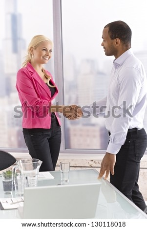 Young female and male business partners shaking hands, smiling. - stock photo