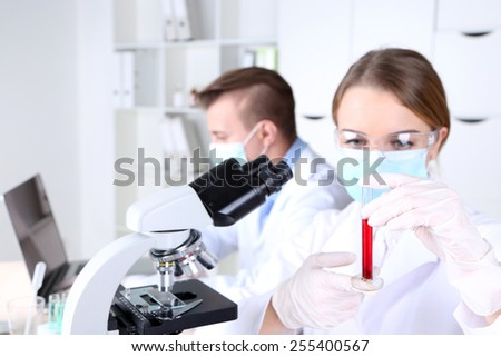 Young female and male scientists  with microscope in laboratory