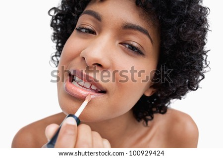 Young female applying lipstick with a lip brush in a concentrated way - stock photo