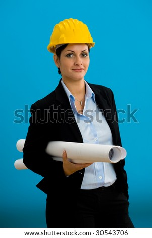 Young female architect in hardhat with blueprint isolated on blue.