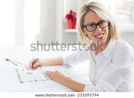 Young female architect sitting at her desk in the office - stock photo