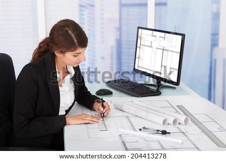 Young female architect working on blueprint at desk in office - stock photo