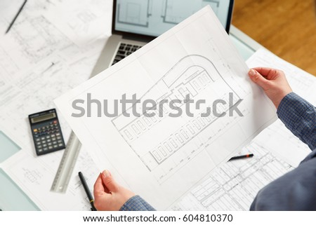 Young female architect  working on blueprint project of new parking lot. Photo concept of work on technical drawings