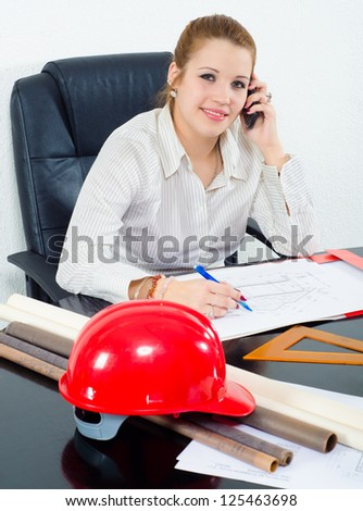 Young female architect working on the project in her office. - stock photo