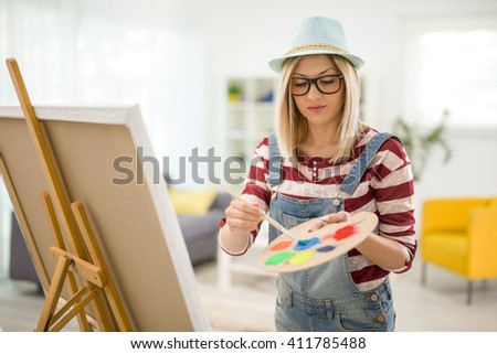 Young female artist mixing colors on a palette and painting on a canvas at home - stock photo
