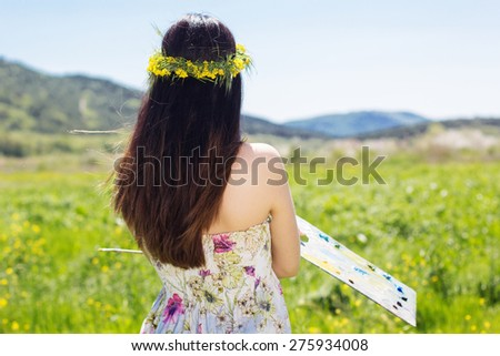 Young female artist painting an floral landscape, summer time