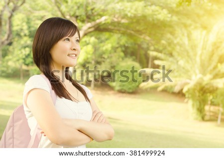 Young female Asian university student standing on campus lawn, with backpack looking away  and smiling. - stock photo