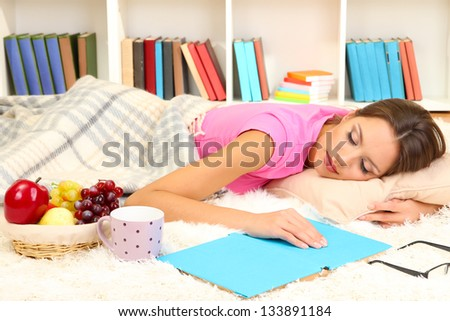 Young female asleep while reading book on floor - stock photo