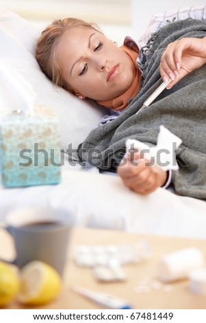 Young female at home caught cold, feeling bad, taking her temperature in bed. - stock photo