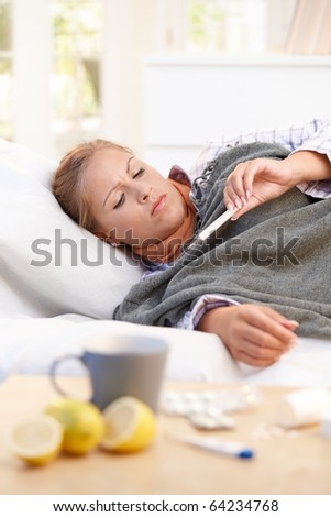 Young female at home having flu, feeling bad, taking her temperature in bed.? - stock photo