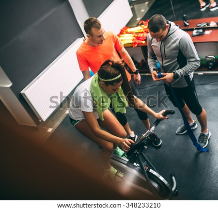 Young female at the gym exercising on the xtrainer machines,driving bike - stock photo