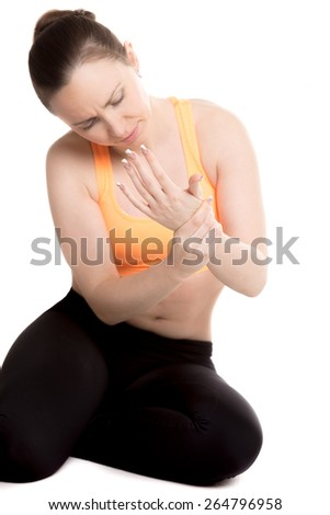 Young female athlete in sportswear touching aching wrist with unhappy expression, hurt after sport training, aching ligament, strained forearm - stock photo