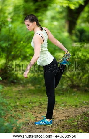 Young female athlete is doing stretching exercise in nature. She is standing on one leg and holding other, stretching her thigh.