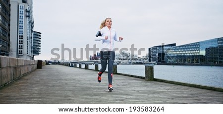 Young female athlete running on boardwalk along the river. Fit young woman jogging along the waterfront. - stock photo