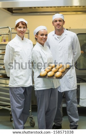 Young female baker presenting some rolls posing with her colleagues