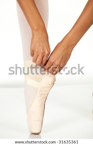 Young female ballet dancer showing how to tie a ballet Pointe Shoe against a white background. NOT ISOLATED