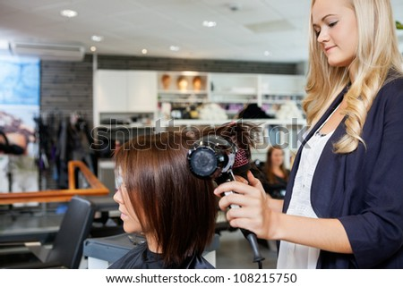 Young female beautician giving a new hair style to woman at parlor - stock photo