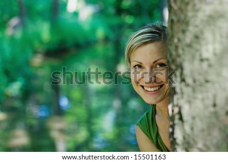 young female behind a tree smiling