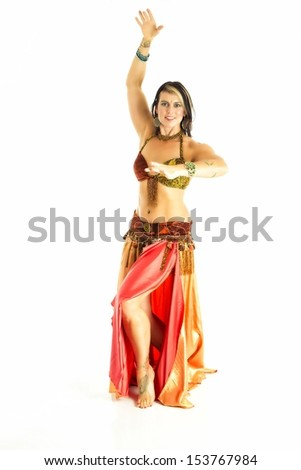 Young female belly dancer with a red and orange costume with gold accents. Isolated on white.