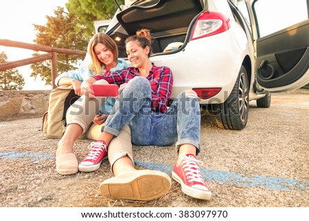 Young female best friends having fun with mobile smart phone at car trip moment - Wanderlust concept during happy travel vacation on the road - Warm late afternoon color tones with main focus on faces - stock photo