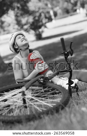 Young female bicyclist with hurt leg sitting on grass in the park - stock photo