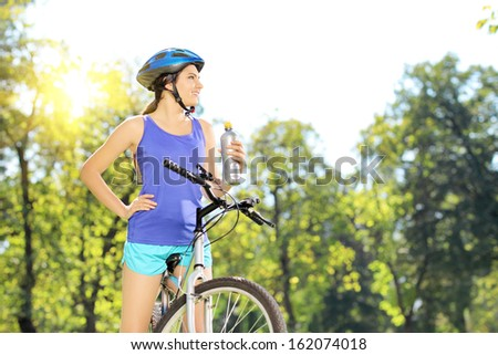 Young female biker posing on a mountain bike outdoor on a sunny day - stock photo