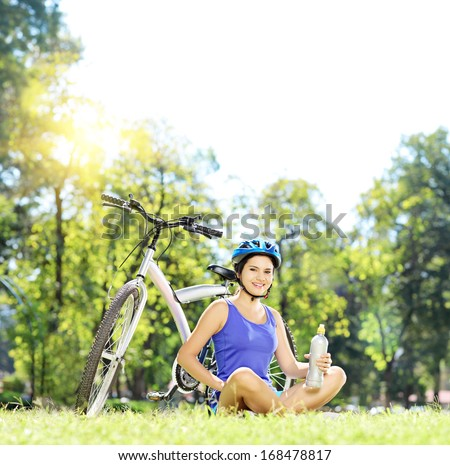 Young female biker sitting on a green grass next to a mountain bike and drinking water, shot with a tilt and shift lens
