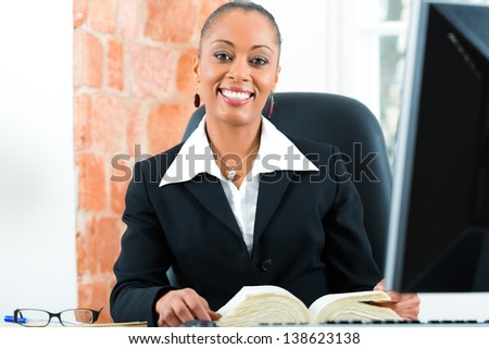 Young female black lawyer working in her office and reading a typical law book in front of a computer - stock photo