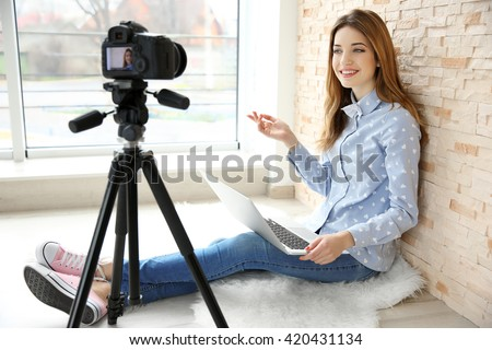 Young female blogger with laptop recording video at home - stock photo