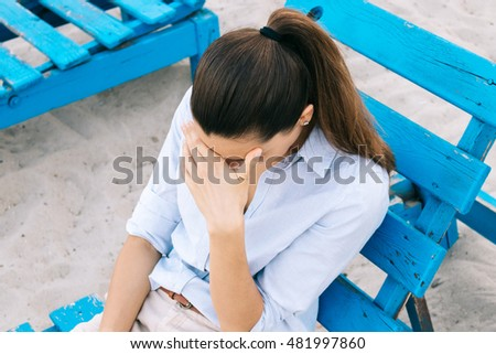 Young female brunette in shirt sitting on a bench on the beach and covers her face with a palm