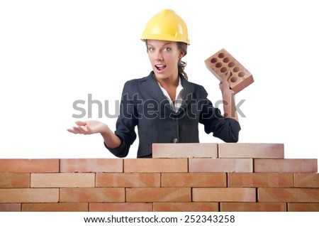 Young female builder near brick wall - stock photo