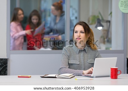 Young female Business Trainee working on Laptop Computer at grey Desk pensively looking aside thinking about new Idea - stock photo