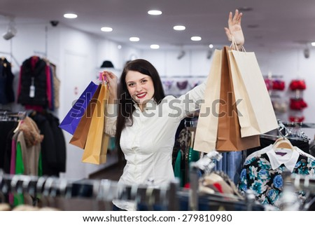 Young female buyer with bags at clothing store - stock photo
