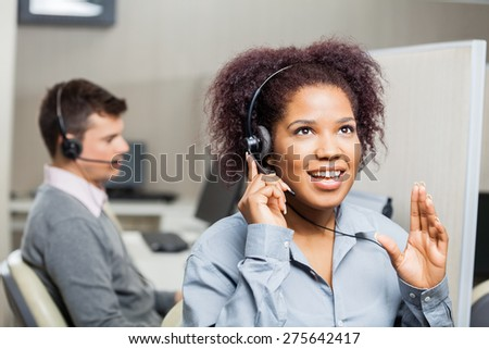 Young female call center agent speaking with costumer at office