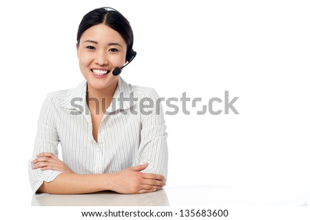 Young female call centre executive sitting at her desk with arms folded. - stock photo