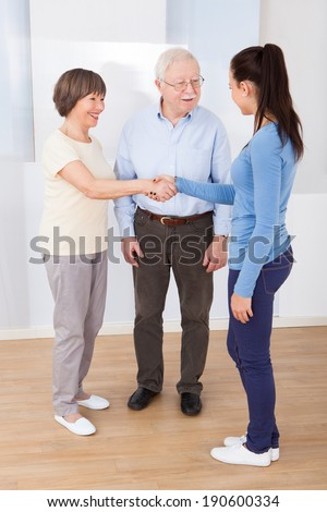 Young female caregiver shaking hands with senior couple at nursing home