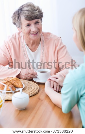 Young female carer keeping company senior woman - stock photo