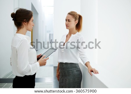 Young female ceo holding touch pad while talking with her partner in modern office interior during work break, couple of a women professional staff using digital tablet for discussing business plan