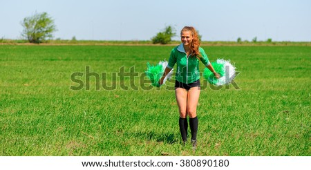 Young female cheerleader in a green jacket on the grass