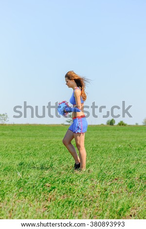 Young female cheerleader wearing blue suite on the grass
