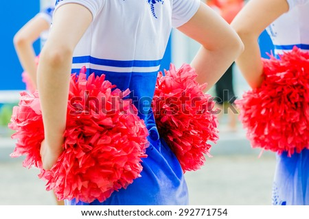 young female cheerleaders holding pom-poms during competitions - stock photo