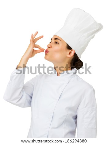 Young female chef kissing her hand to show perfection over white background. Vertical shot. - stock photo