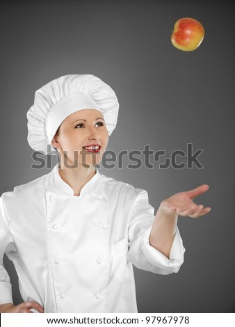 Young female chef playing with apple - stock photo