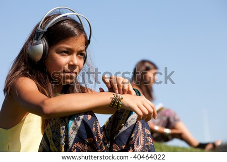 young female child listening music outdoor