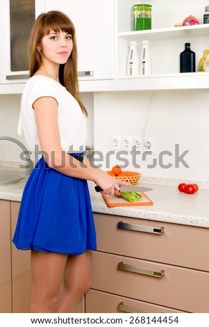 Young female chopping celery on the kitchen, a few tomatoes lying on the counter - stock photo