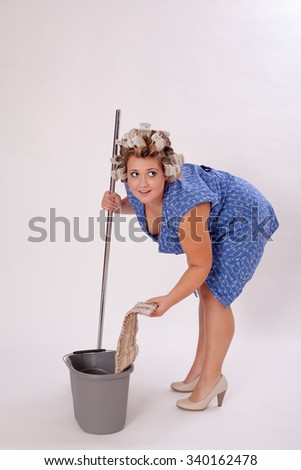 Young Female Cleaner with Hair Curler Wearing Shoes, Holding Cleaning Materials, Looking Into the Distance Against Gray Background.