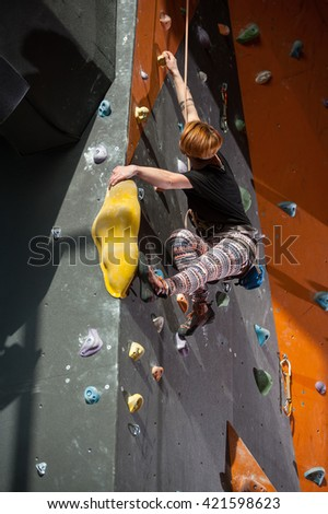 Young female climber is climbing up on indoor rock-climbing wall, bottom view