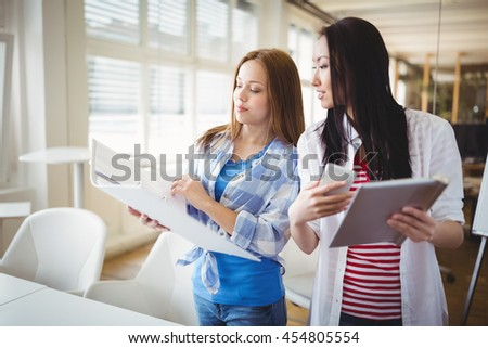 Young female colleagues discussing with files in creative office