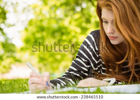 Young female college student doing homework in the park - stock photo