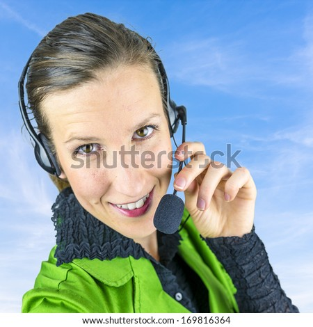 Young female complaint department employee with headset on background of blue sky. - stock photo